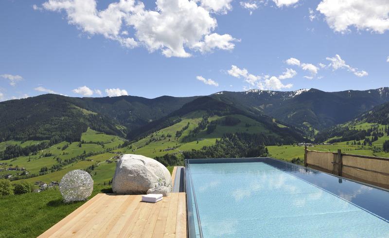 Infinity Pool mit Ausblick auf die Berge- Luxusurlaub auf der Alm