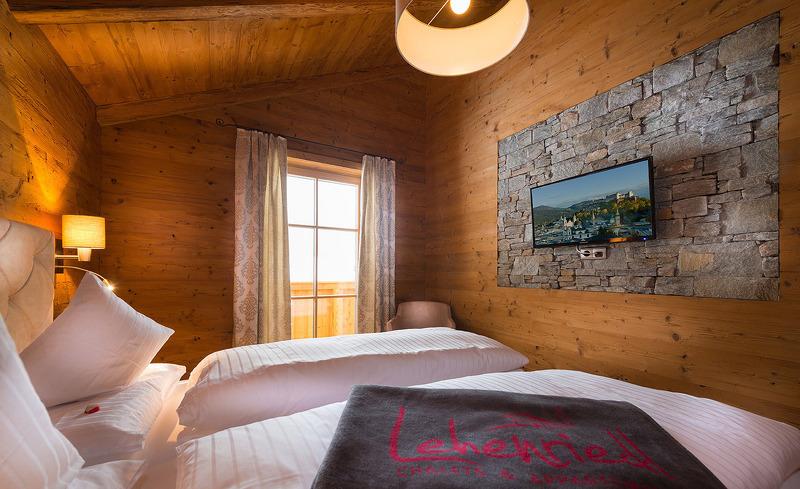 Das komfortable Schlafzimmer ist ausgestattet mit Fernseher und Balkon- Chaleturlaub in Salzburg