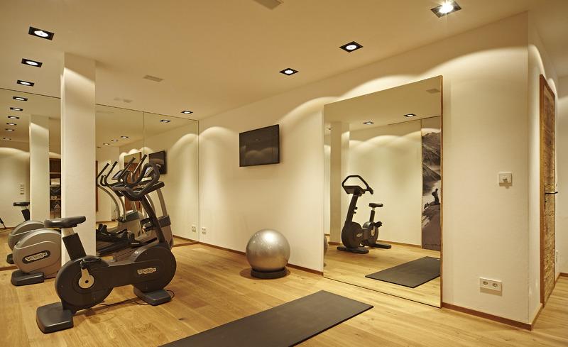 Hüttenurlaub Deluxe- Fitnessbereich mit hochwertigen Geräten im Chaletdesign