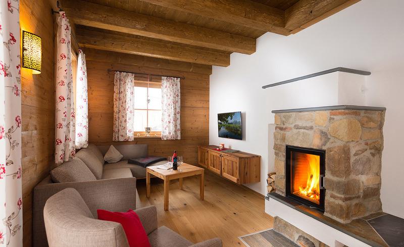 Verbringen Sie kuschelige Stunden zu zweit vor dem offenen Kamin im Wohnbereich Ihres privaten Chalets