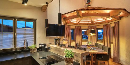 Familienurlaub in Bayern- Der Koch- und Essbereich verfügt über eine vollausgestattete Küche einen Flatscreen-TV und eine große Essbank